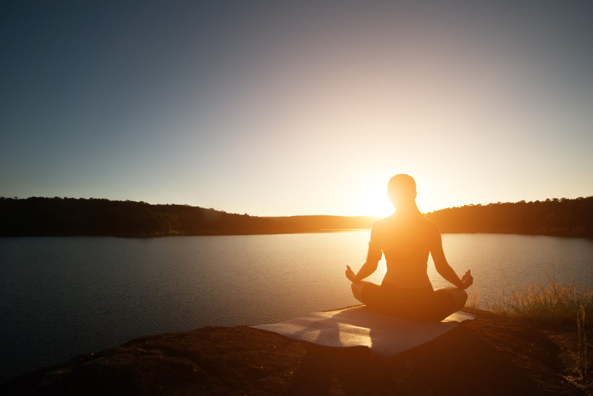 woman doing yoga with a sunset